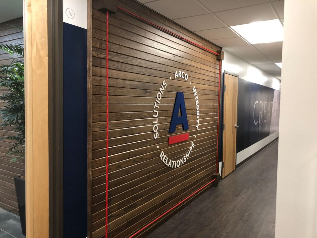 Wooden wall with red rope bordering it, has letter A in the middle with ARCOs logo