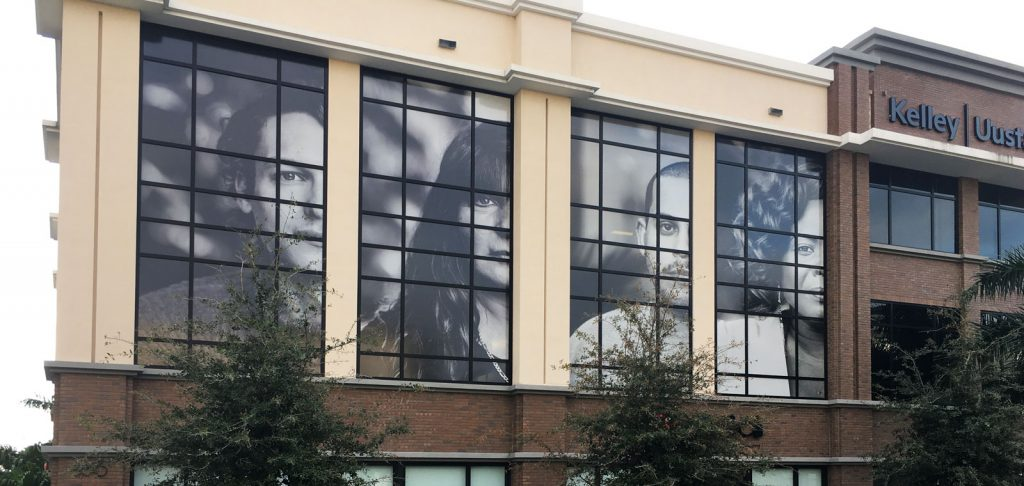 Exterior view of a large set of windows with photographs applied to the outside.